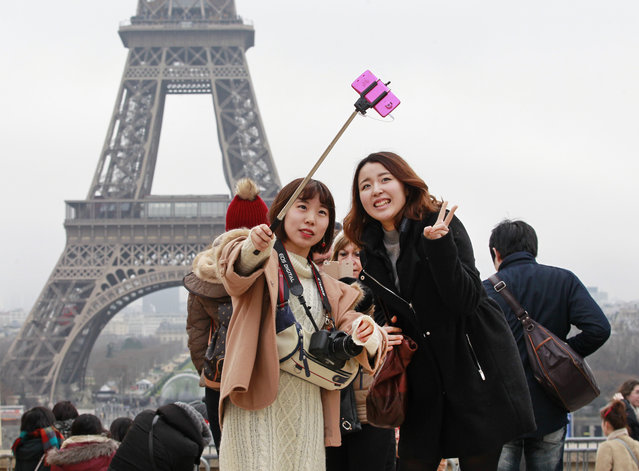 Tourists use a selfie stick on the Trocadero Square, with  the Eiffel Tower in background, in Paris, Tuesday, January 6, 2015. (Photo by Remy de la Mauviniere/AP Photo)