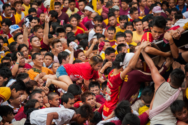 Black Nazarene devotees clamber on top of one another to to touch the cross on January 9, 2015 in Manila, Philippines. The Feast of the Black Nazarene culminates in a day long procession on January 9 as barefoot devotees march to see and touch the image of the Black Nazarene. (Photo by Dondi Tawatao/Getty Images)
