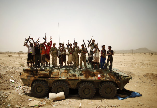 Members of Yemen's elite Republican Guard and pro-army tribesmen gather for a group photo atop a military vehicle as they secure a road leading to Lawdar town in the southern province of Abyan June 19, 2012. (Photo by Khaled Abdullah/Reuters)