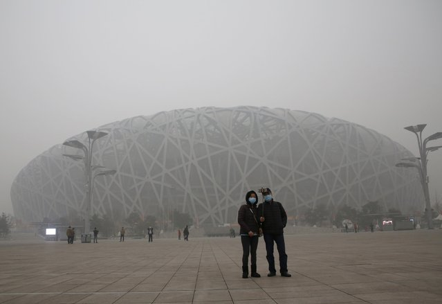 """Visitors wearing protective masks take a selfie in front of the National Stadium, also known as the """"Bird's Nest"""", on an extremely polluted day as hazardous, choking smog continues to blanket Beijing, China December 1, 2015. (Photo by Kim Kyung-Hoon/Reuters)"""