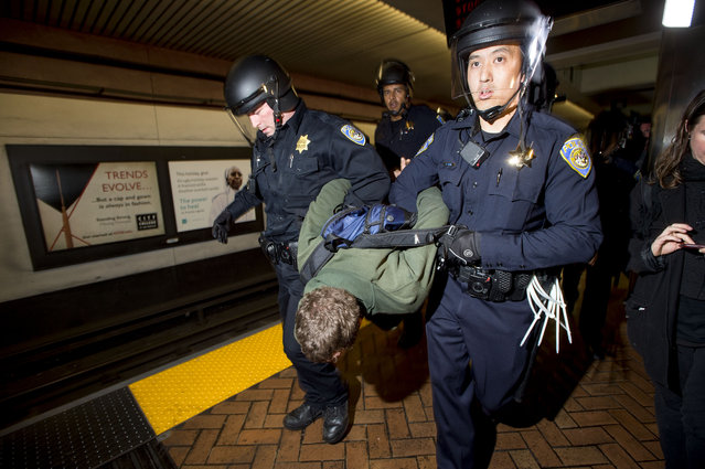 Police officers arrest a protester who banged a spoon on a subway car during a demonstration at the Bay Area Rapid Transit Montgomery station on Friday, January 16, 2015, in San Francisco. About 80 demonstrators rallied in support of 14 anti-police violence protesters arrested in November for blocking trains at an Oakland BART station. (Photo by Noah Berger/AP Photo)