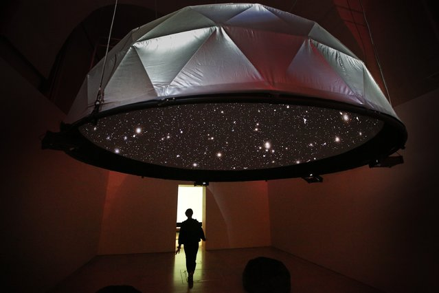 A visitor walks past the 'Black Shoals: Dark Matter' projection at the Big Bang Data exhibition at Somerset House on December 2, 2015 in London, England.  The projection displays stars which  represent live stock market activity. (Photo by Peter Macdiarmid/Getty Images for Somerset House)