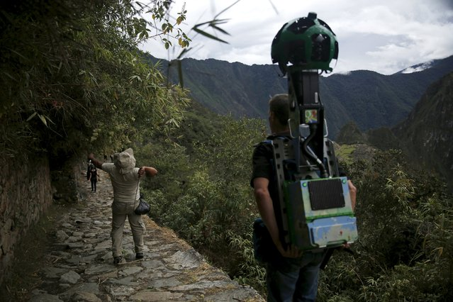 Tech Lead Manager for Google Maps, Daniel Filip (R) waits while carrying the Trekker, a 15-camera device, as a worker cuts tree branches to clear the road to map the Inca citadel of Machu Picchu for Google Street View in Cuzco, Peru, August 12, 2015. (Photo by Pilar Olivares/Reuters)