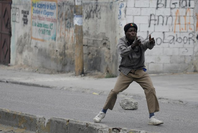 A protestor gestures towards Haitian National Police (PNH) officers (not pictured) during a demonstration demanding the resignation of Haiti's President Jovenel Moise, at the 217th anniversary of the Battle of Vertieres, the last major battle of Haitian independence from France, in Port-au-Prince, Haiti, November 18, 2020. (Photo by Andres Martinez Casares/Reuters)