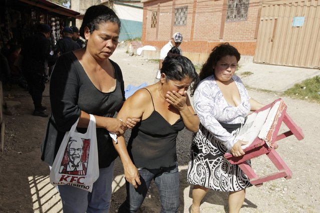 The relative (C) of a shooting victim reacts as she arrives at the crime scene at Las Torres neighbourhood in Tegucigalpa January 16, 2015. Unknown assailants gunned down two youth and injured one in an attack at the gang-infested area of the city, local media reported. (Photo by Jorge Cabrera/Reuters)