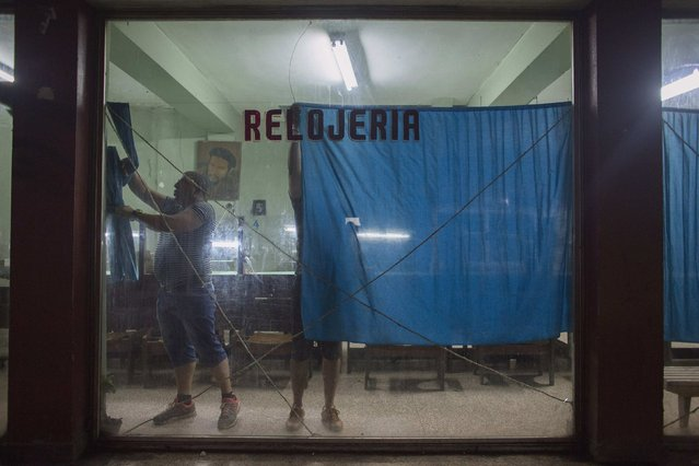 Artur Aliaga, 45 (L), who works fixing watches, closes the window at the state run watch repair shop at the end of the day in downtown Havana, January 20, 2015. (Photo by Alexandre Meneghini/Reuters)