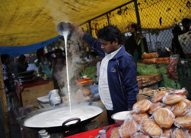 A vendor pours milk to cool it-off before serving it to the customers at a makeshift roadside shop in New Delhi January 15, 2015. (Photo by Anindito Mukherjee/Reuters)