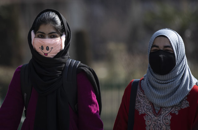 Kashmiri students wearing face masks arrive as colleges reopened eleven months after being closed due to the coronavirus pandemic in Srinagar, Indian controlled Kashmir, Monday, February 15, 2021. (Photo by Mukhtar Khan/AP Photo)