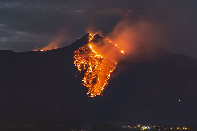 Lava flows from the Mt Etna volcano, near Catania in Sicily, southern Italy, early Tuesday, February 23, 2021. The explosion started before midnight on Monday night, provoking a huge eruption plume that rose for several kilometers from the top of Etna, as reported by The National Institute of Geophysics and Volcanology, Etneo Observatory. (Photo by Salvatore Allegra/AP Photo)