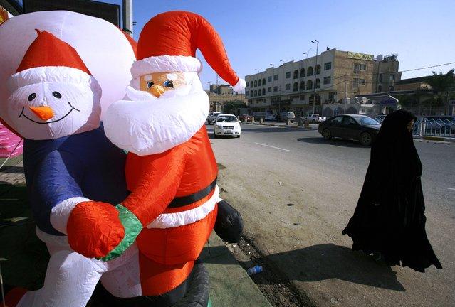 An Iraqi Muslim woman walks past Christmas decorations for sale in the Shiite holy city of Najaf on December 17, 2015. (Photo by Haidar Hamdani/AFP Photo)