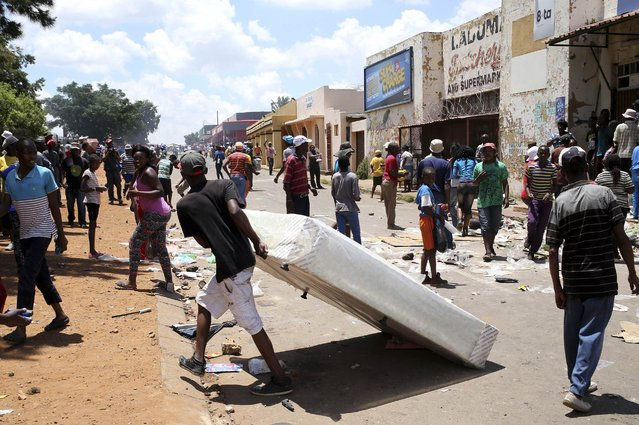 A man drags a bed he looted from a shop believed to be owned by a foreigner, during service delivery protests in Mohlakeng, west of Johannesburg February 4, 2015. (Photo by Siphiwe Sibeko/Reuters)