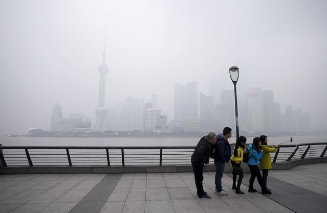 Tourists take selfies at the bund as the financial district of Pudong (rear) is seen amid heavy smog, in Shanghai, China, December 11, 2015. (Photo by Aly Song/Reuters)