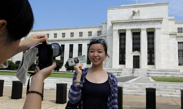 Chinese student Leyna Liu from Shanghai poses with a fake million dollar bill in front of the Federal Reserve building in Washington, in this August 22, 2012 file photo. Sellers of Western luxury brands eager to capitalize on the new wealth of Chinese consumers are showering attention on mainland students in the United States, even as sales in China falter. (Photo by Larry Downing/Reuters)