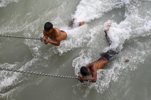 Hindu devotees take a holy dip in the waters of the River Ganges on the eve of Shahi Snan (grand bath) on Maha Shivratri festival during the ongoing religious Kumbh Mela festival in Haridwar on March 10, 2021. (Photo by Prakash Singh/AFP Photo)