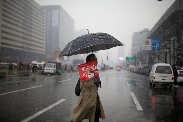"A man holding an umbrella and placard that reads ""Step down Park Geun-hye"" crosses a road during a protest calling for Park Geun-hye to step down as it snows in Central Seoul, South Korea, November 26, 2016. (Photo by Kim Kyung-Hoon/Reuters)"