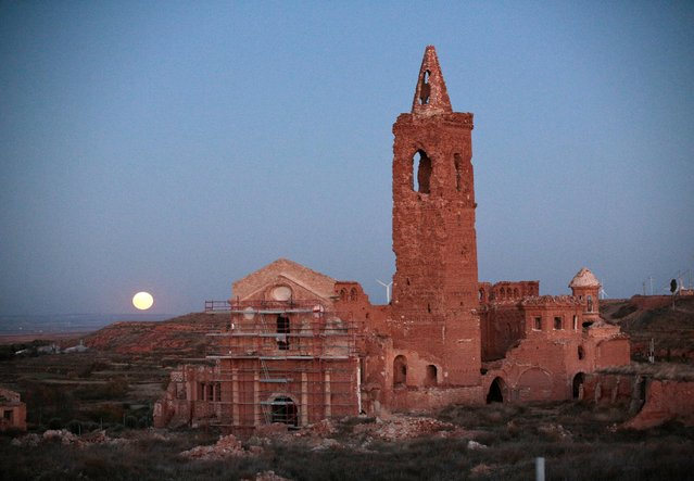 The moon rises behind the San Martin de Tours church in the old village of Belchite, in northern Spain, November 14, 2016. (Photo by Andrea Comas/Reuters)