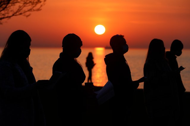 Parishioners are silhouetted against the rising sun as they gather and pray during an Easter sunrise service held by Park Community Church Sunday, April 4, 2021, at North Avenue Beach in Chicago. (Photo by Shafkat Anowar/AP Photo)