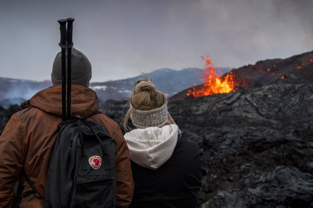 People watch the Lava flows from an eruption of a volcano on the Reykjanes Peninsula in southwestern Iceland on Wednesday, March 31, 2021. Iceland's latest volcano eruption is still attracting crowds of people hoping to get close to the gentle lava flows. (Photo by Marco Di Marco/AP Photo)