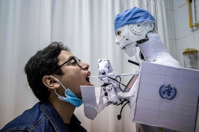 A prong extending from a remote-controlled robot prototype approaches the mouth of a volunteer to extract a throat swab sample, as part of a self-funded project to assist physicians in running tests on suspected COVID-19 coronavirus patients in a bid to limit human exposure to disease-carriers, at a private hospital in Egypt's Nile delta city of Tanta, on March 20, 2021. (Photo by Khaled Desouki/AFP Photo)