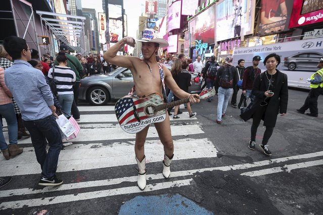 One of the Naked Cowboys poses for photos in Times Square during unseasonably warm weather on Christmas eve in the Manhattan borough of New York, December 24, 2015. (Photo by Carlo Allegri/Reuters)