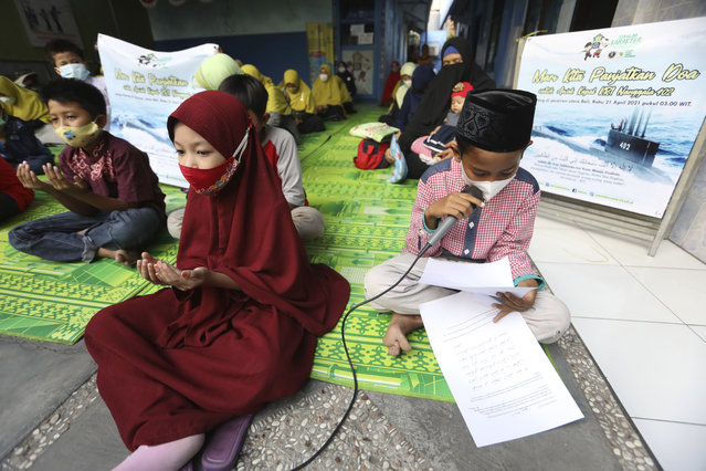 Students pray during a vigil for the crew of Indonesian Navy submarine KRI Nanggala that went missing while participating in a training exercise on Wednesday, at an elementary school in Surabaya, East Java, Indonesia, Friday, April 23, 2021. Indonesian navy ships scoured the waters off Bali on Friday as they raced against time to find the submarine that disappeared two days ago and has less than a day's supply of oxygen left for its 53 crew. (Photo by Trisnadi/AP Photo)