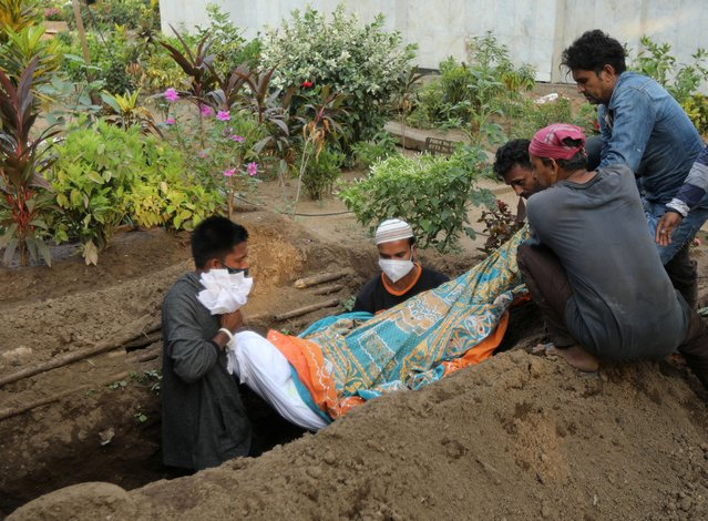 Gayesh Ansari, looks at the body of his 8 months pregnant wife, Gulshan Ansari as he lowers her body into a grave after she died from the coronavirus disease (COVID-19) at a graveyard in Mumbai, India on April 28, 2021. (Photo by Francis Mascarenhas/Reuters)