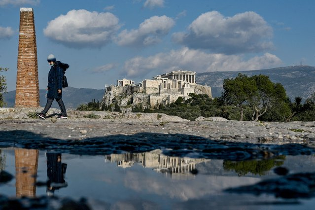 A woman walks on a hill overlooking the ancient Acropolis in Athens on April 1, 2021, a day after Greece said it would reopen most shops and relax leisure restrictions despite persistently high Covid-19 deaths and infections that have put its health system under major strain. (Photo by Louisa Gouliamaki/AFP Photo)