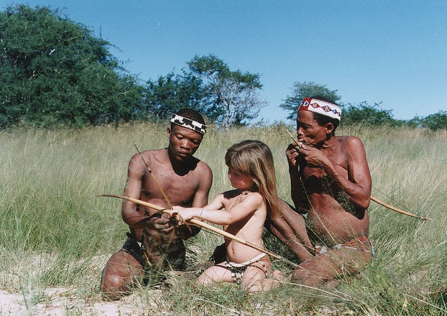 Tippi, aged 6 with Tkui and another man of the San Bushmen of northern Namibia. Tkui is teaching Tippi to use a bow and arrow in Namibia, 1996. (Photo by Sylvie Robert/Barcroft Media)