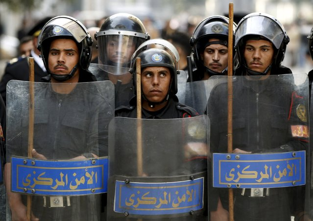Riot police keep watch as they hold shields during clashes with protesters in Cairo January 26, 2011. (Photo by Goran Tomasevic/Reuters)