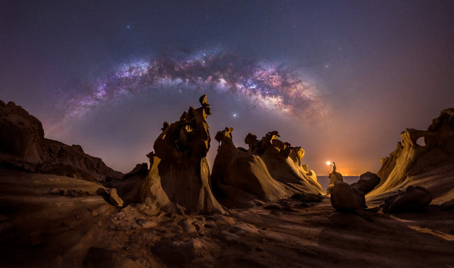 """Night lovers; Hormozgan province, Iran. """"In this picture, you can see the Milky Way rising on a fascinating spring night on the Persian Gulf coast. The stunning cliffs of this area make every viewer imagine and even talk to them! The light pollution from a faraway city was quite strong, so it was a challenging post-processing process. I'm a nightscaper who tries to achieve an artistic look in my images, and in this image, I tried to convey and capture the magic of this location"""". (Photo by Mohammad Hayati/Milky Way Photographer of the Year)"""
