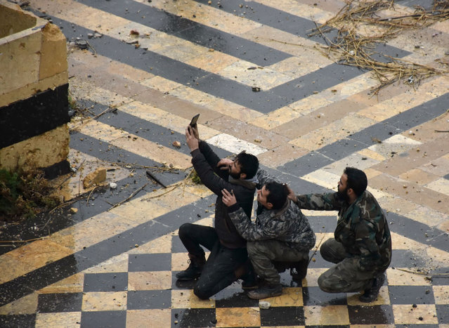 Syrian pro-government forces take a selfie in the courtyard of the ancient Umayyad mosque in the old city of Aleppo on December 13, 2016. (Photo by George Ourfalian/AFP Photo)