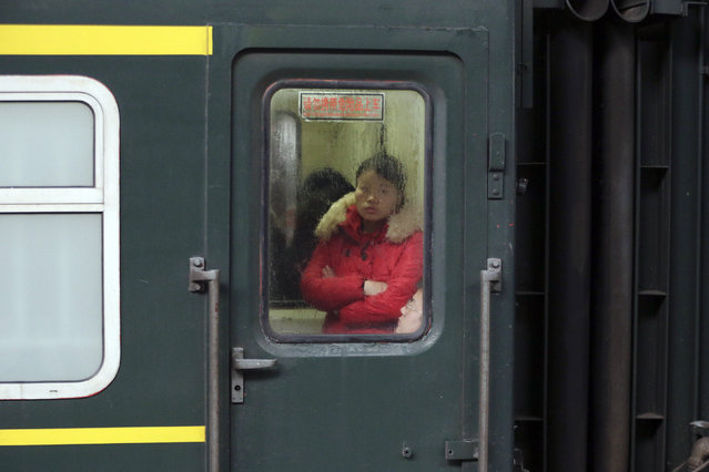 A passenger looks from inside a train travelling from Shanghai to Shijiazhuang at the station in Wuxi after migration for the annual Chinese Lunar New Year and Spring Festival began. Picture taken January 27, 2016. (Photo by Aly Song/Reuters)