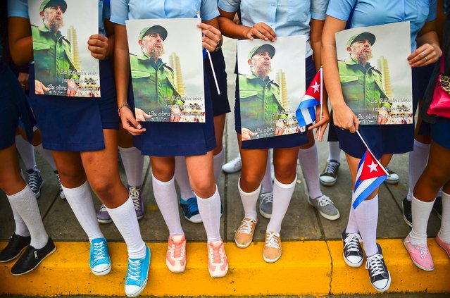 High school students wait for the urn with the ashes of Cuban leader Fidel Castro to drive through Santa Clara on December 1, 2016, during its four-day journey across the island for the burial in Santiago de Cuba. (Photo by Ronaldo Schemidt/AFP Photo)