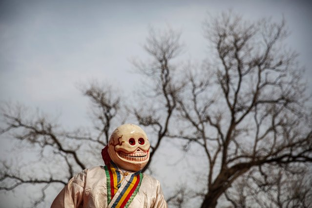 A Tibetan Buddhist monk in a ghost costume takes part in the Beating Ghosts ritual at the Yonghe Temple in Beijing, China on March 19, 2015. The ritual is held on the the 29th day of the first month after the Tibetan New Year and is meant to expel evil spirits. (Photo by Kevin Frayer/Getty Images)