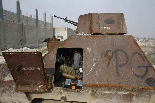 A fighter of the Kurdish People's Protection Units (YPG) sits in an armoured vehicle in the northern Syrian town of Kobani January 28, 2015. (Photo by Osman Orsal/Reuters)