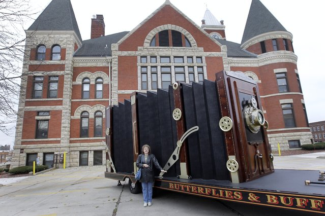 A woman poses for her husband alongside a giant camera Thursday, November 7, 2013 outside the Historic Green County Courthouse in Monroe, Wis. Chicago photographer Dennis Manarchy created what's being called the world's largest camera. (Photo by Mark Hoffman)