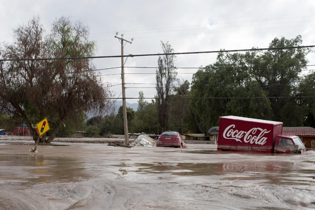 Cars and a truck lie half submerged in the mud in a street  in Copiapo, Chile, Thursday, March 26, 2015. (Photo by Pablo Sanhueza/AP Photo)