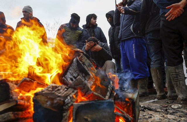 Migrants try to warm up around a brazier in a muddy field at a camp of makeshift shelters for migrants and asylum-seekers from Iraq, Kurdistan, Iran and Syria, called the Grande Synthe jungle, near Calais, France, February 3, 2016. European Union countries on Wednesday approved a 3 billion euro ($3.32 billion) fund for Turkey to improve living conditions for refugees there in exchange for Ankara ensuring fewer of them migrate on to Europe. (Photo by Yves Herman/Reuters)