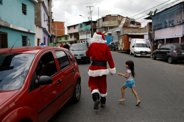 """Richard Gamboa walks in a street of the slum Cota 905 during the """"Santa en las calles"""" (Santa in the streets) event donating toys, food, and clothes in Caracas, Venezuela on December 1, 2018. (Photo by Marco Bello/Reuters)"""
