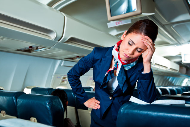 Young air stewardess suffering from headache on an airplane. (Photo by Izabela Habur/Getty Images)