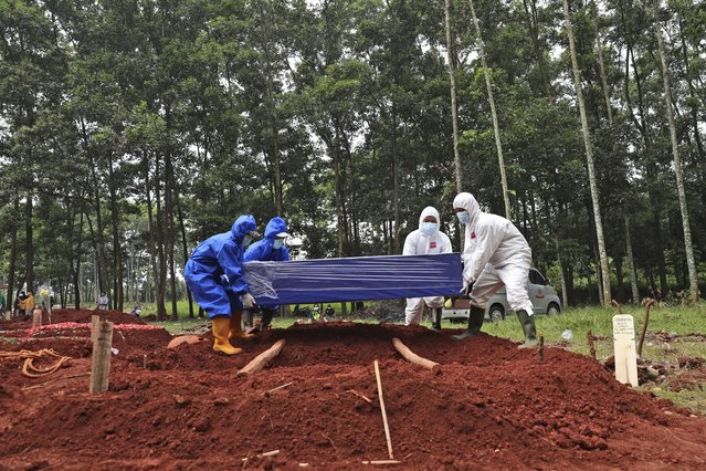 Workers in protective suits prepare to lower a coffin containing the body of a COVID-19 victim into a grave at Cipenjo cemetery in Bogor, West Java, Indonesia, Wednesday, July 14, 2021. The world's fourth most populous country has been hit hard by an explosion of COVID-19 cases that have strained hospitals on the main island of Java. (Photo by Achmad Ibrahim/AP Photo)