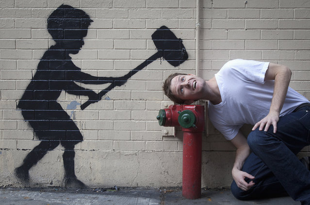 A man jokingly poses with a new installation of British graffiti artist Banksy's art in New York, October 20, 2013. (Photo by Carlo Allegri/Reuters)