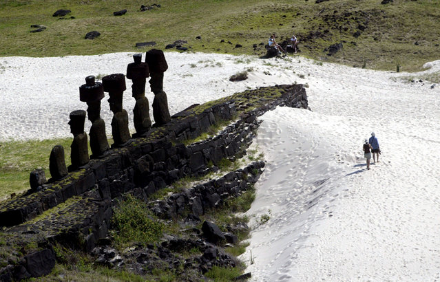 """Tourists walk next to """"Moai"""" statues in the Anakena beach on Easter  Island, 4,000 km (2486 miles) west of Santiago, October 29, 2003.  Easter Island's mysterious """"Moai"""", gigantic busts carved out of  volcanic rock, are in danger of being destroyed by years of tropical  rains and wind as well as careless humans and farms animals. Experts have called on the international community to commit funds to preserve the monoliths, whose mystery draws tourists to the world's most remote inhabited island. (Photo by Carlos Barria/Reuters)"""