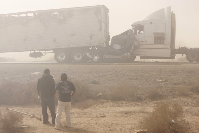Two people look at the scene of a multiple vehicle collisions along Interstate-10 during a dust storm near Casa Grande, Arizona, December 22, 2009. (Photo by Joshua Lott/Reuters)