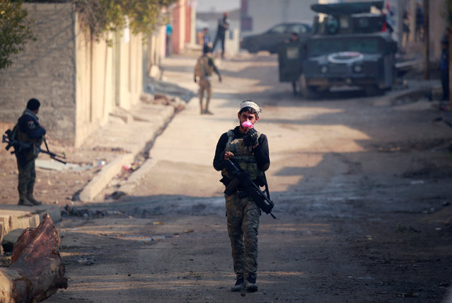 A member of Iraqi rapid response forces holds a flower during battle with Islamic State militants in the Mithaq district of eastern Mosul, Iraq, January 4, 2017. (Photo by Thaier Al-Sudani/Reuters)