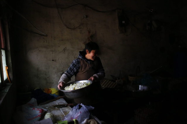 Wang Hui prepares food for students in the Democracy Elementary and Middle School kitchen in Sitong town, Henan province December 3, 2013. (Photo by Carlos Barria/Reuters)