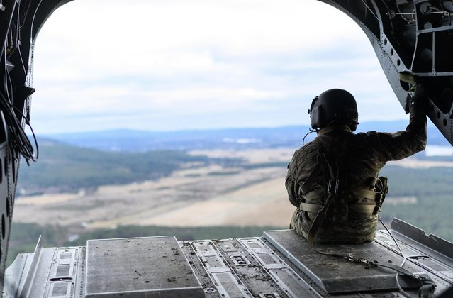 A member of the US Army aircrew surveys the Norwegian countryside from the rear of a US Army Chinook helicopter during pre-exercise integration training on October 27, 2018 in Norway. (Photo by Leon Neal/Getty Images)