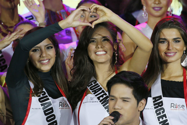 Miss Universe contestants Connie Jimenez of Ecuador, left, and Virginia Argueta of Guatemala, form a heart as Filipino singer Gerald Santos serenades them prior to joining an NGO to pack meals for distribution to the needy in suburban Pasay city southeast of Manila, Philippines Wednesday, January 18, 2017. (Photo by Bullit Marquez/AP Photo)