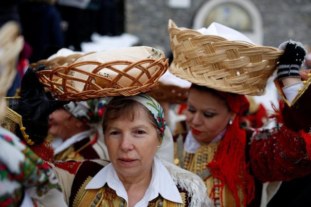 Women dressed in traditional folk costumes balance baskets of bread on their heads during Epiphany day celebration in Bitushe village, Macedonia January 19, 2017. (Photo by Ognen Teofilovski/Reuters)