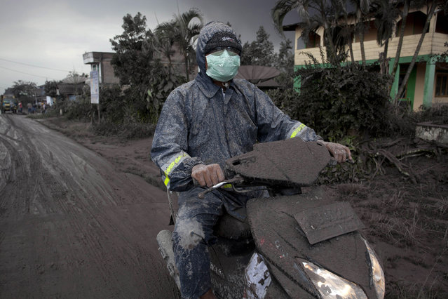 An ash covered a motorcyclist as drives on a road covered with ash following a further eruption of the Mount Sinabung on January 4, 2014 in Karo District, North Sumatra, Indonesia. (Photo by Ulet Ifansasti/Getty Images)